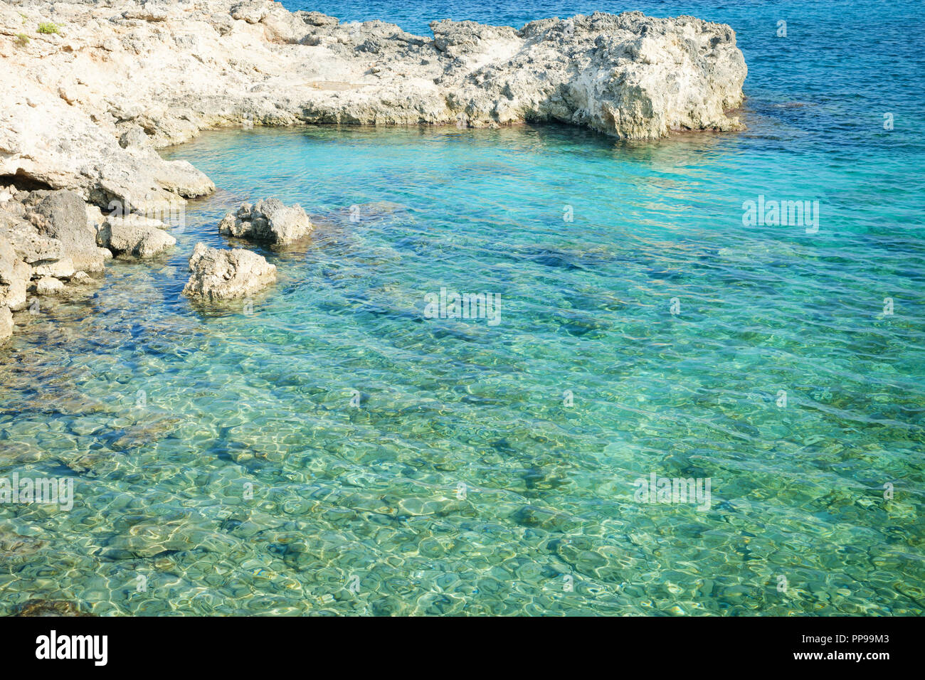 Blue water in a rocky cove near Ognina, Siracusa, Sicily, Italy Stock Photo
