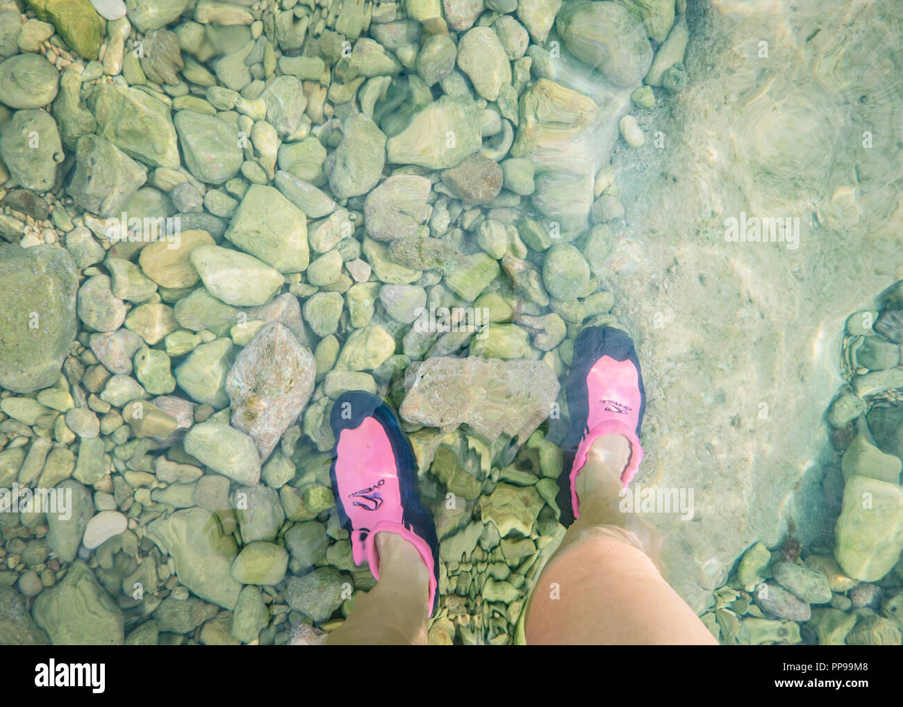 Woman's feet in diving shoes in shallow water on rocky beach, Ognina, Sicily Stock Photo