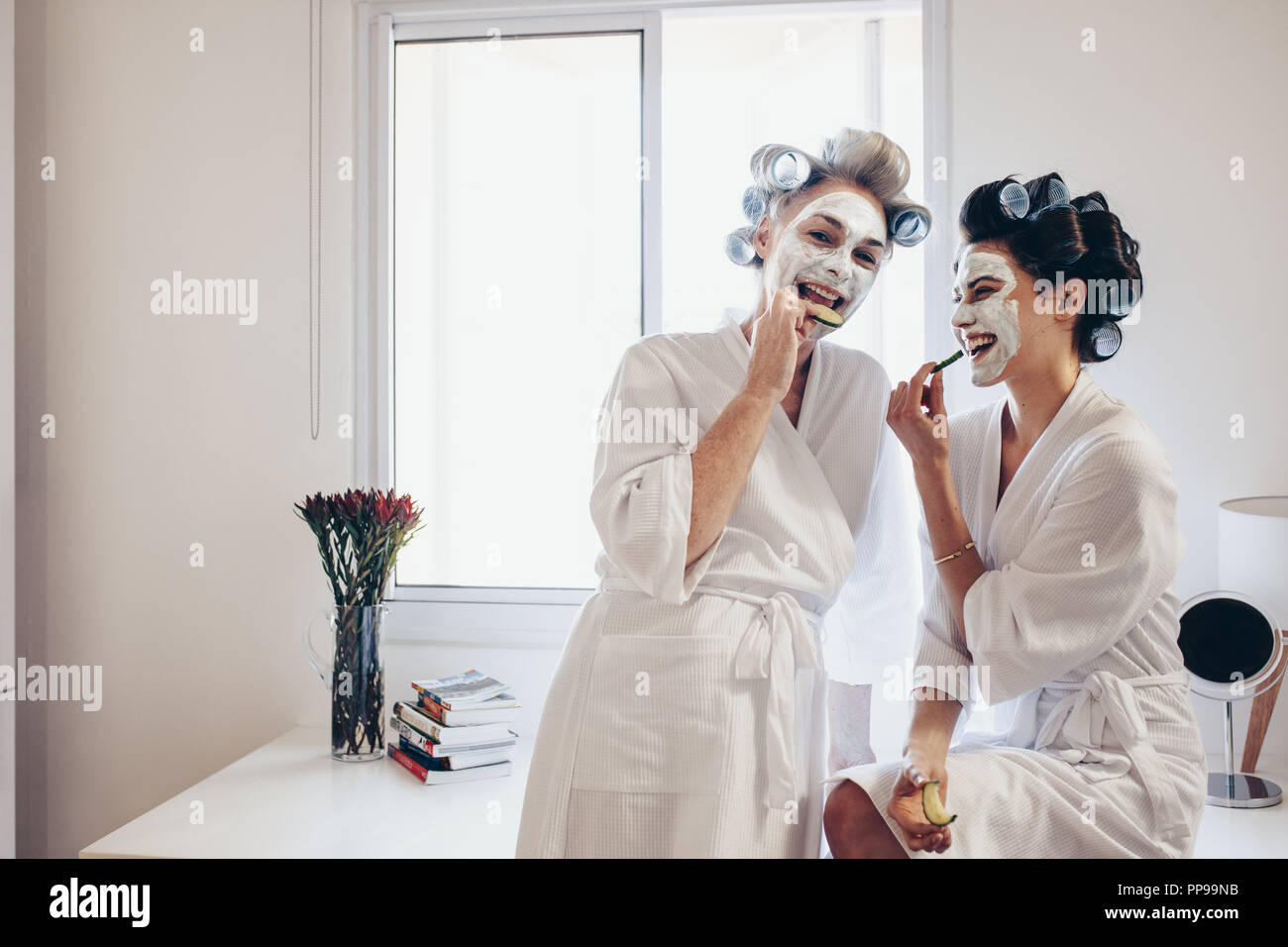 Happy Women In Bathrobes Standing At Home Eating Slices Of Cucumber Smiling Women Wearing Curling Rollers To Their Hair And Face Pack Having Fun At H Stock Photo Alamy