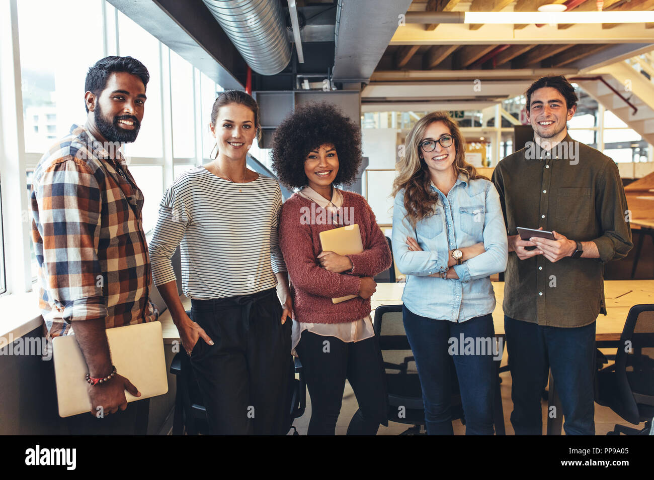 Happy coworkers standing in office holding laptops and tablets. Multiethnic group of business colleagues standing together in office. Stock Photo