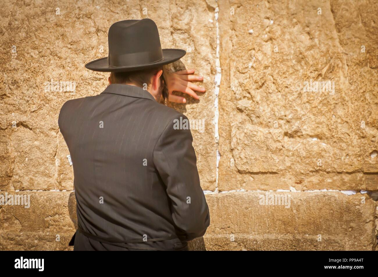 Jewish Orthodox man praying at the Wailing wall. Religious Jewish man seen from the back, Orthodox Jew praying at the Western wall (Wailing wall), Jew - Stock Image