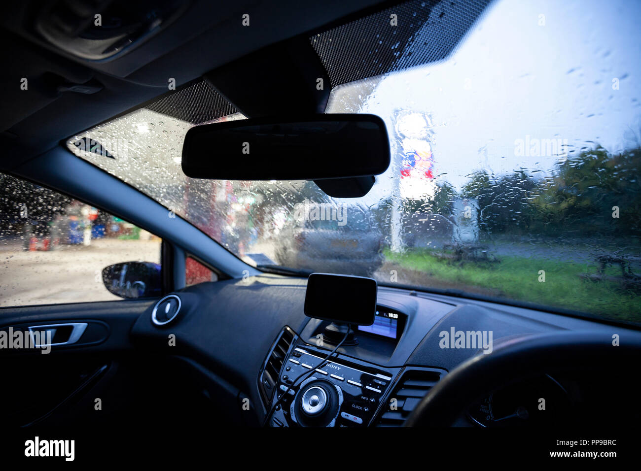Inside a Ford Fiesta car cockpit, parked by the roadside on a rainy day. - Stock Image