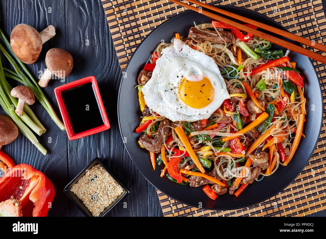 Sweet and savory  korean Japchae: bouncy cellophane noodles with mixed crunchy vegetables: spinach, red bell pepper, onion, carrot, garlic, shiitake m - Stock Image