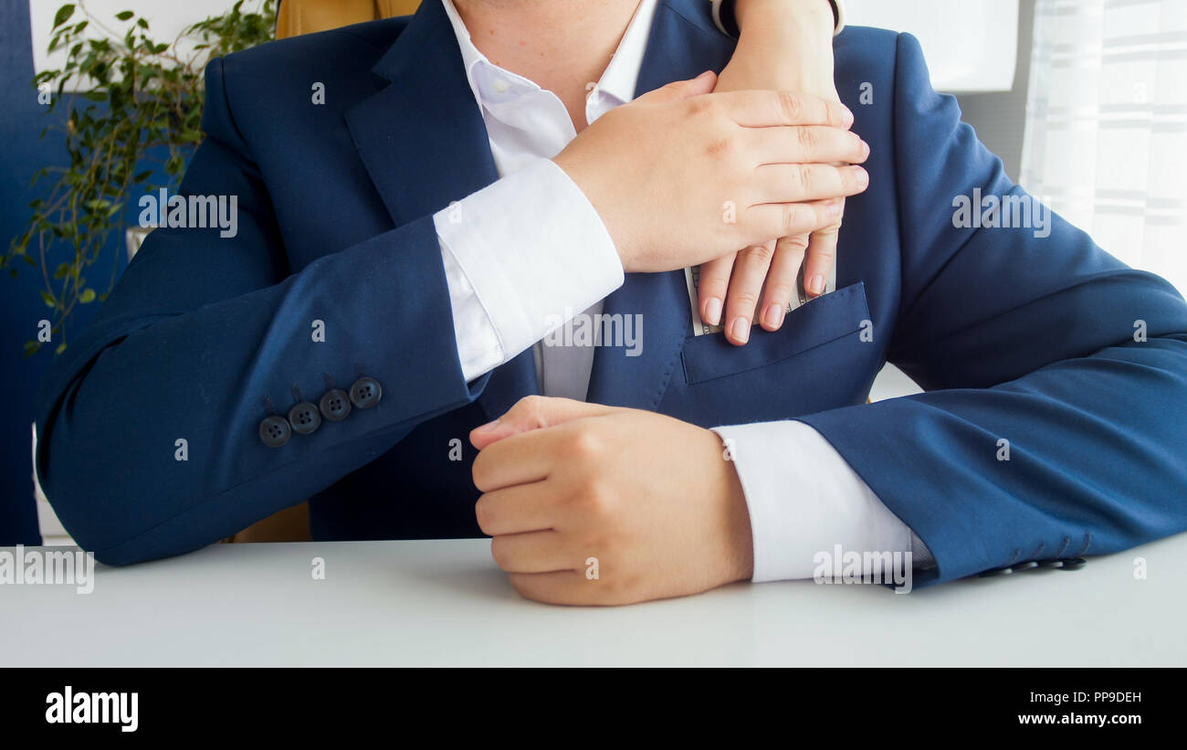 Closeup image of businessman grabing thief's hand stealing money from his pocket Stock Photo