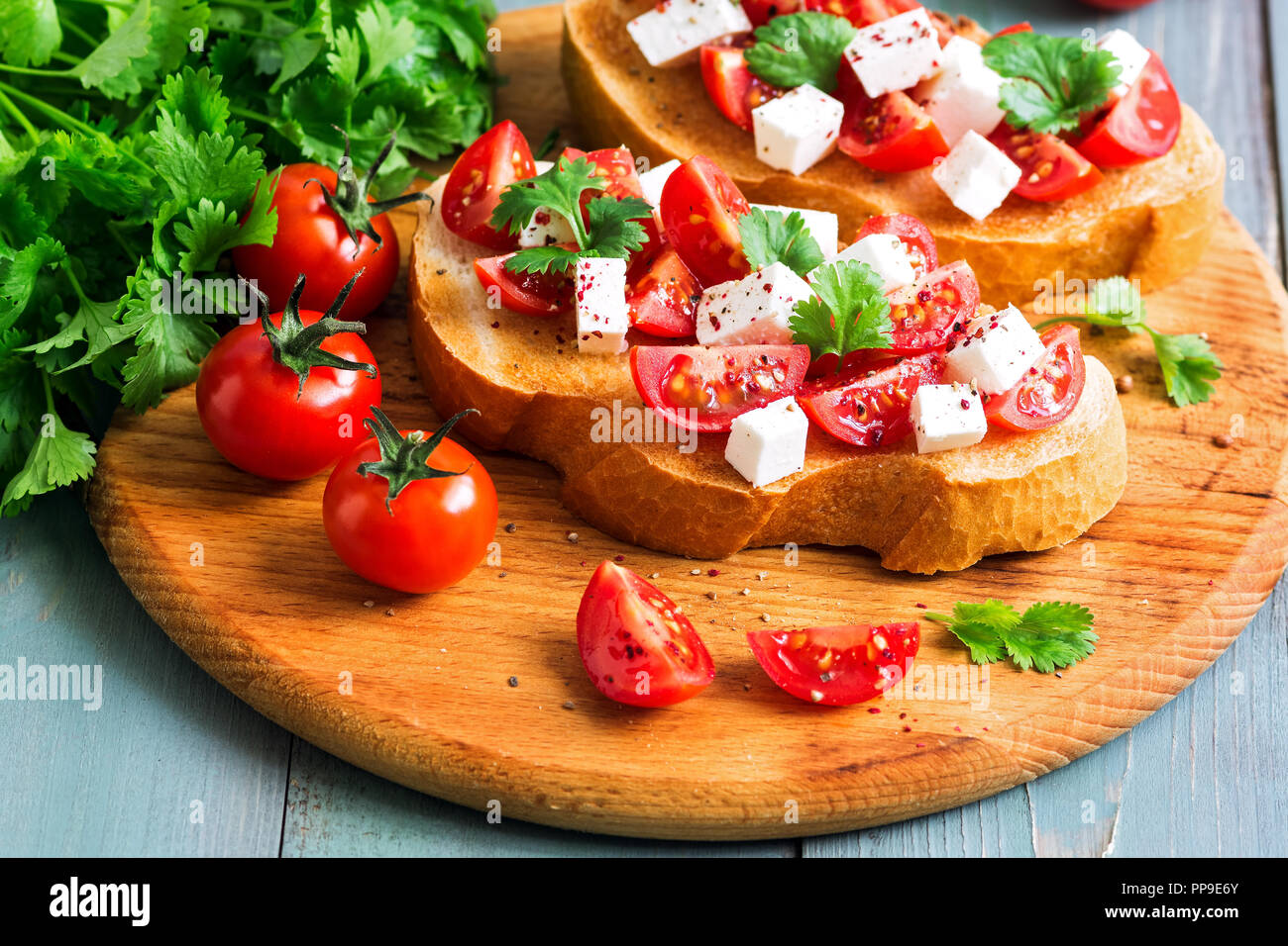 Bruschetta with tomatoes, cheese and greens on toasted bread. Traditional Italian food. Selective focus - Stock Image