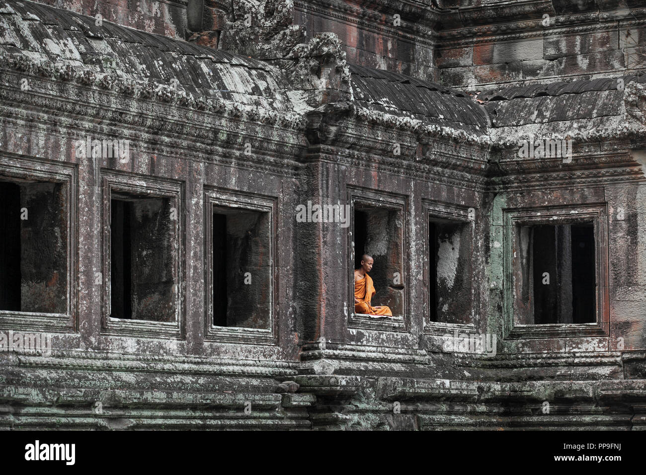 Buddhist monk meditating in window of temple building at Angkor Wat complex in Siem Reap, Cambodia Stock Photo
