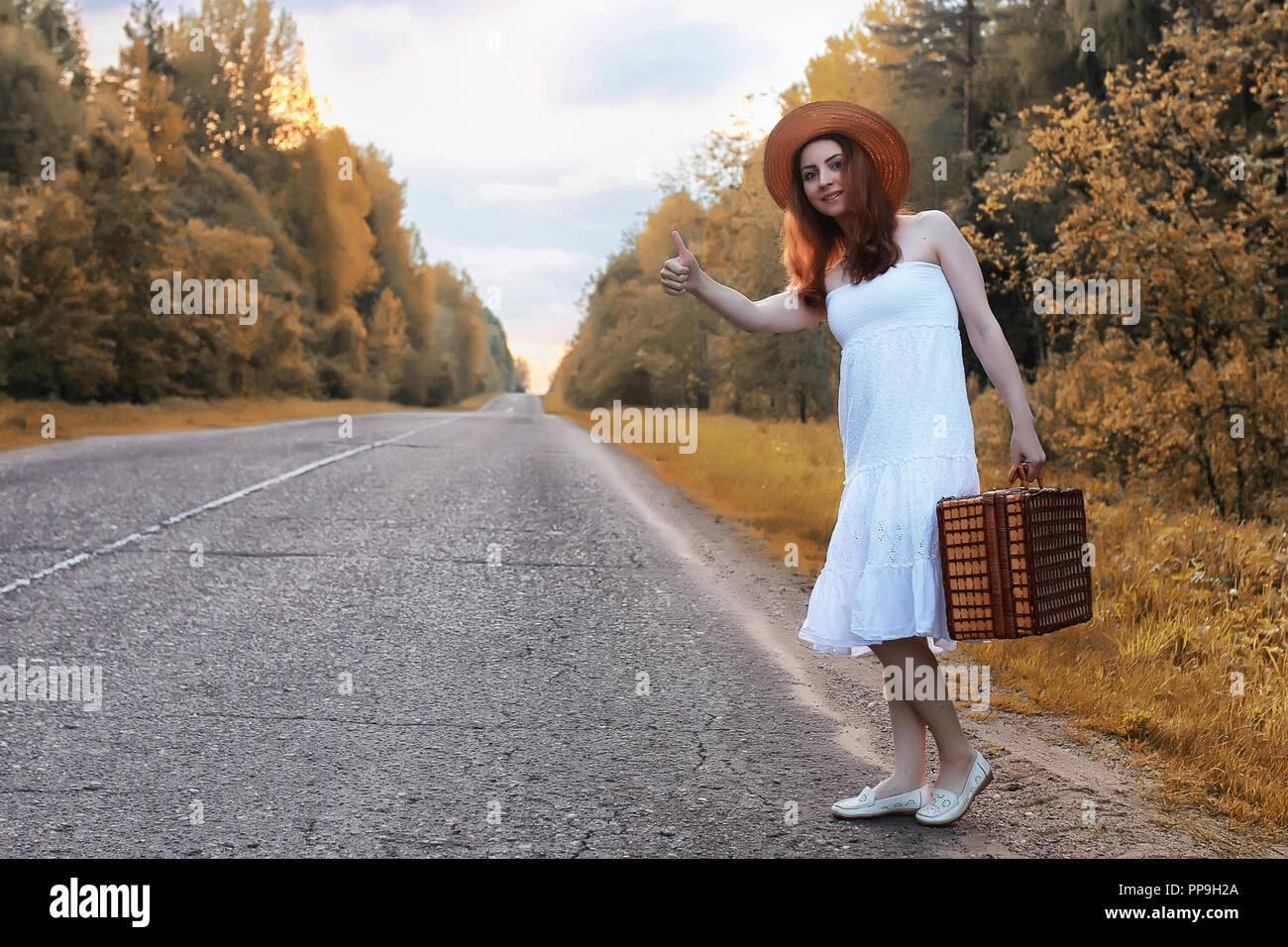 autumn park girl in white sundress and a wicker suitcase walking - Stock Image