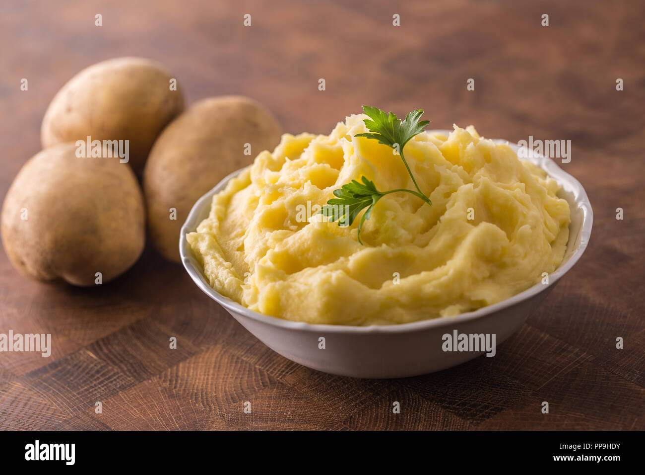 Mashed potatoes in bowl decorated with parsley herbs. - Stock Image
