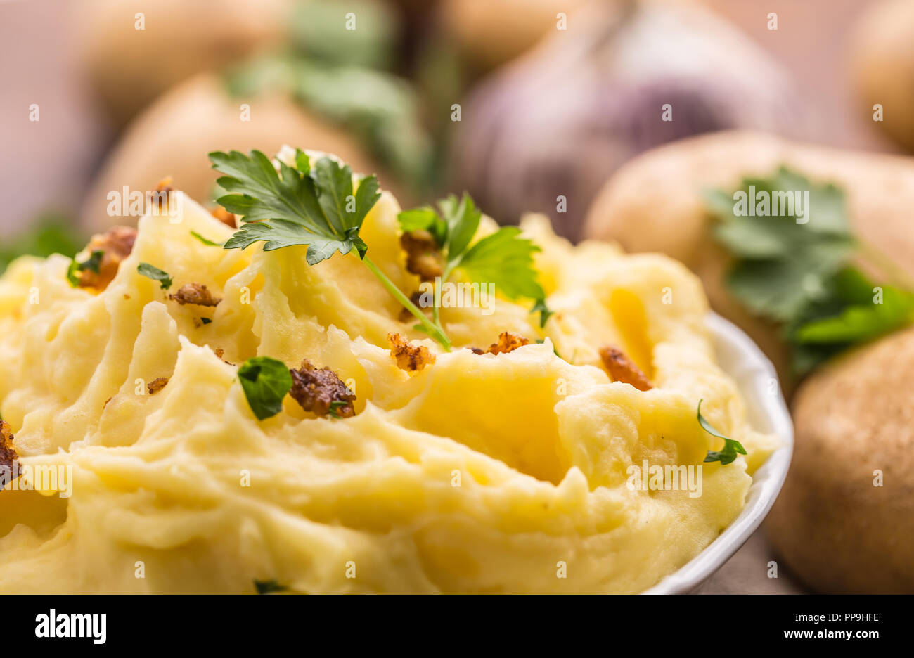 Mashed potatoes in bowl decorated parsley herbs and roasted bacon pieces. - Stock Image