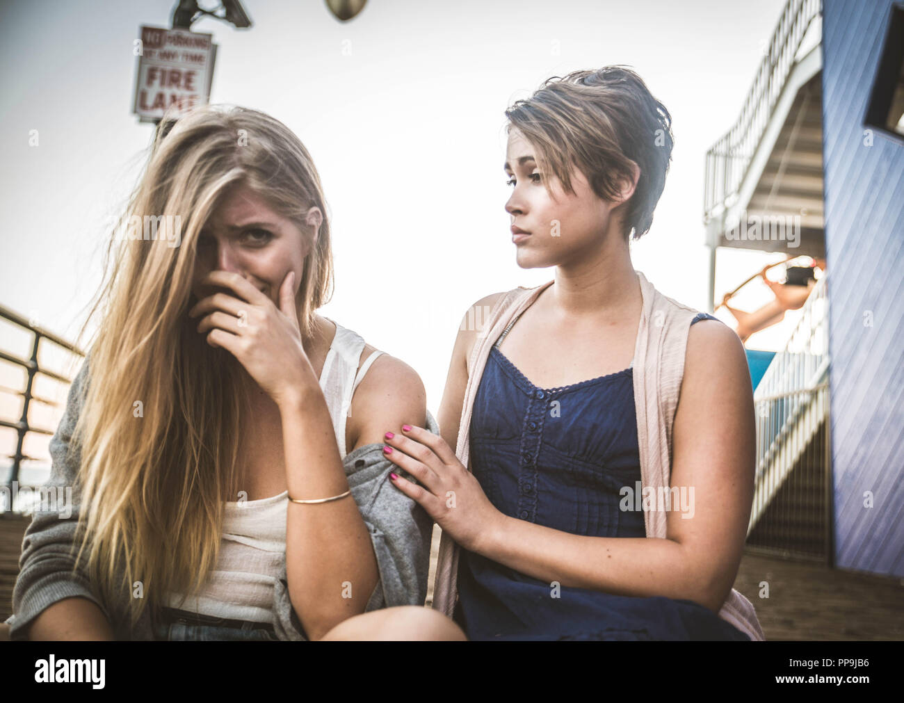 Young woman is sad crying and being consoled by friend - Stock Image