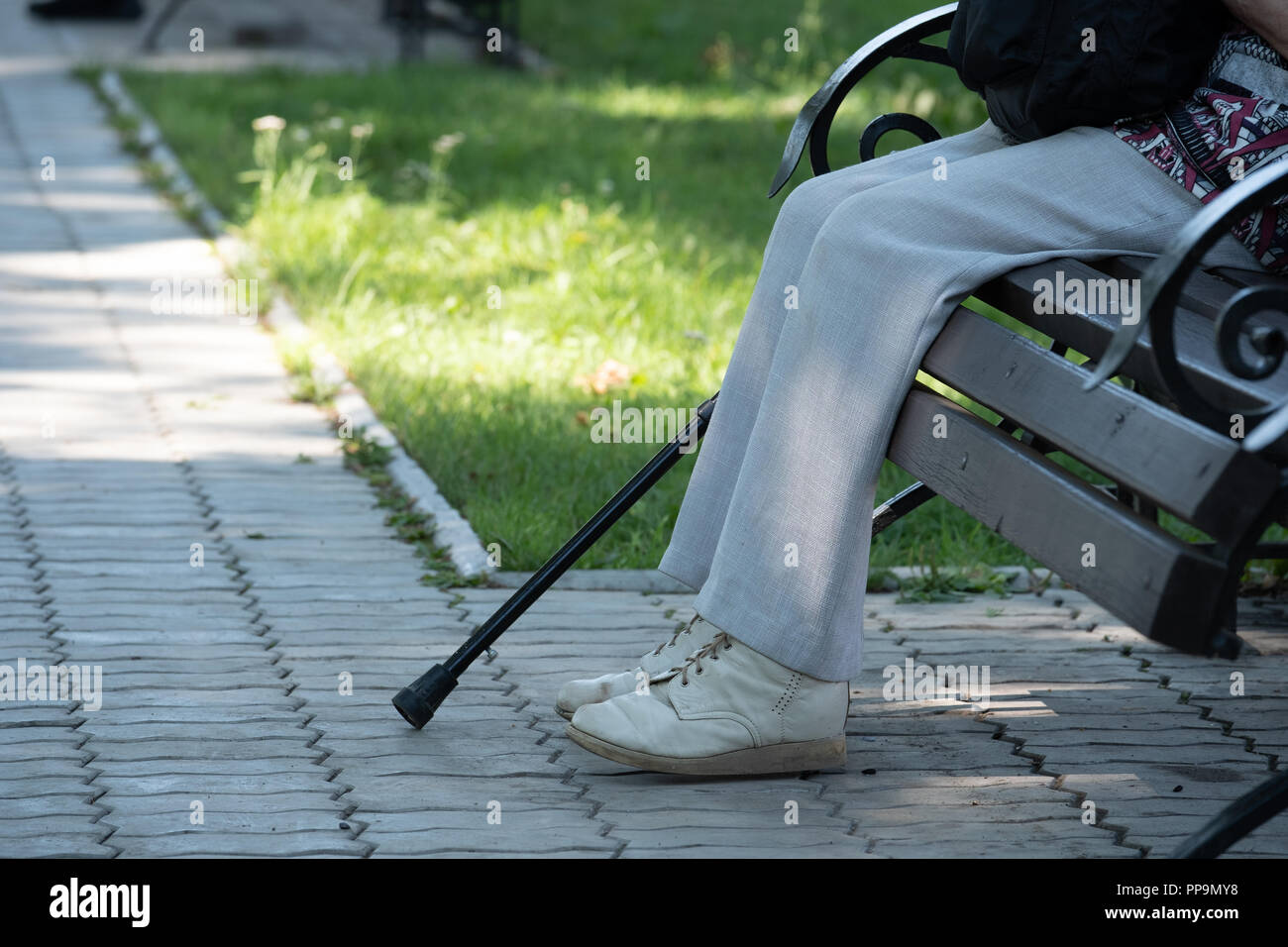 On the image of a foot, a crutch and a bench in the park. On the image of a leg in old pants, shod in old shoes, a crutch and a bench in the park. - Stock Image