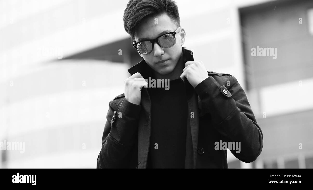 Black White photo of Asian young man outdoors posing Stock