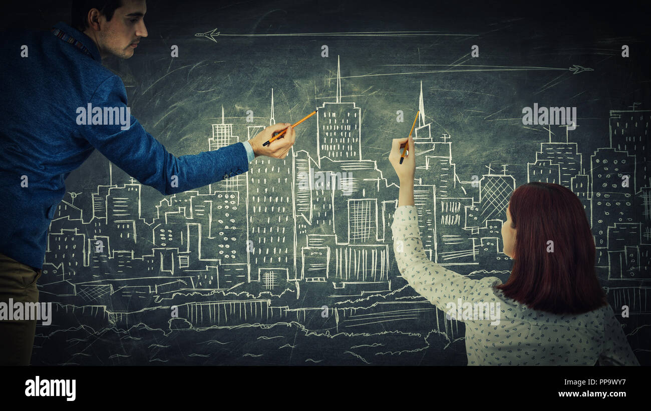 Man and woman sharing thoughts together drawing a city on a blackboard. Urbanistic planning, people idea exchange, business partnership and teamwork i - Stock Image