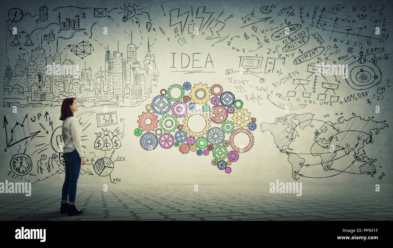 Side view of a pensive young woman looking at the wall with colorful brain made of cogwheel. Unique mind and genius concept. - Stock Image