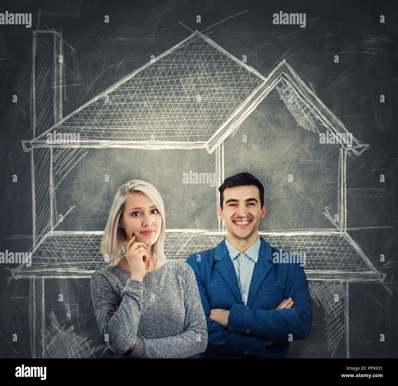 Young couple dreaming of own home, sharing thoughts together as a chalk house sketch drawn over blackboard. - Stock Image