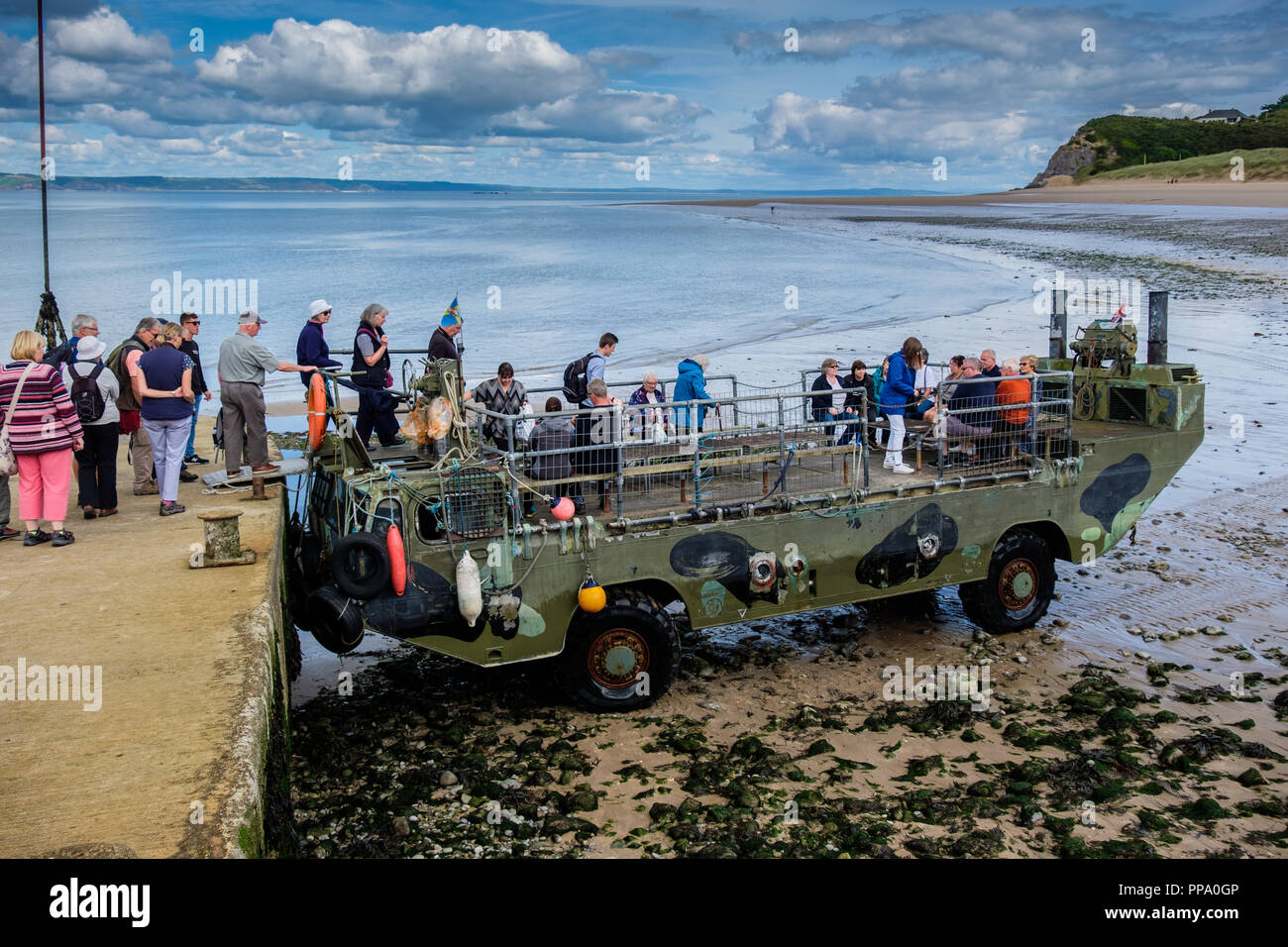 Amphibious vehicle shuttling people between jetty and boats at low tide on Caldey Island, Pembrokeshire, Wales - Stock Image