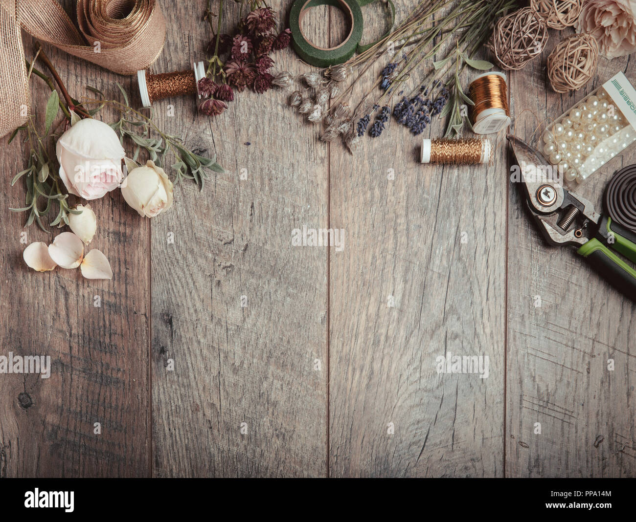 Florist equipment with flowers on wooden background, top view - Stock Image
