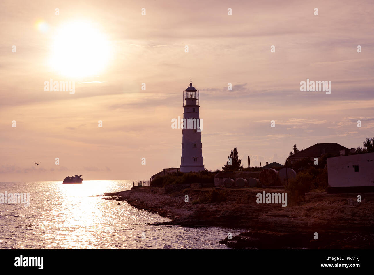 Lighthouse searchlight beam near ocean at sunset. Lighthouse at sunset in the twilight in clear weather - Stock Image