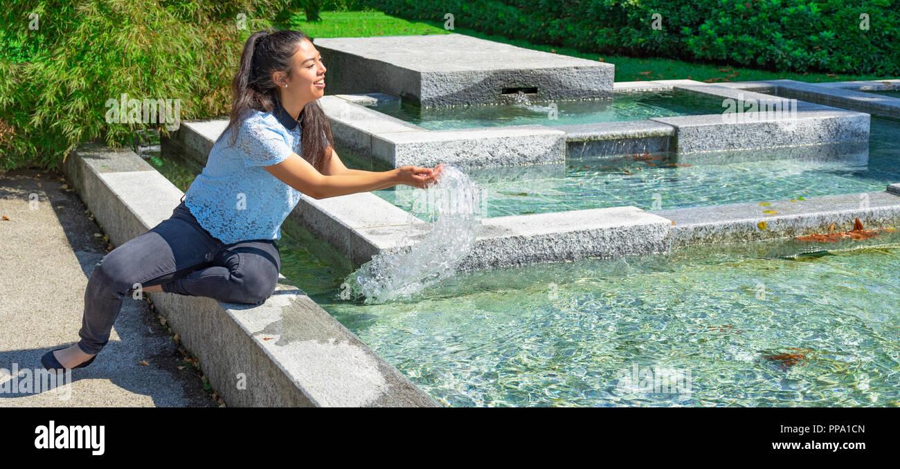 Girl playing with fountain water - Mädchen, das mit Brunnenwasser spielt -  Ragazza che gioca con l'acqua della fontana - Stock Image