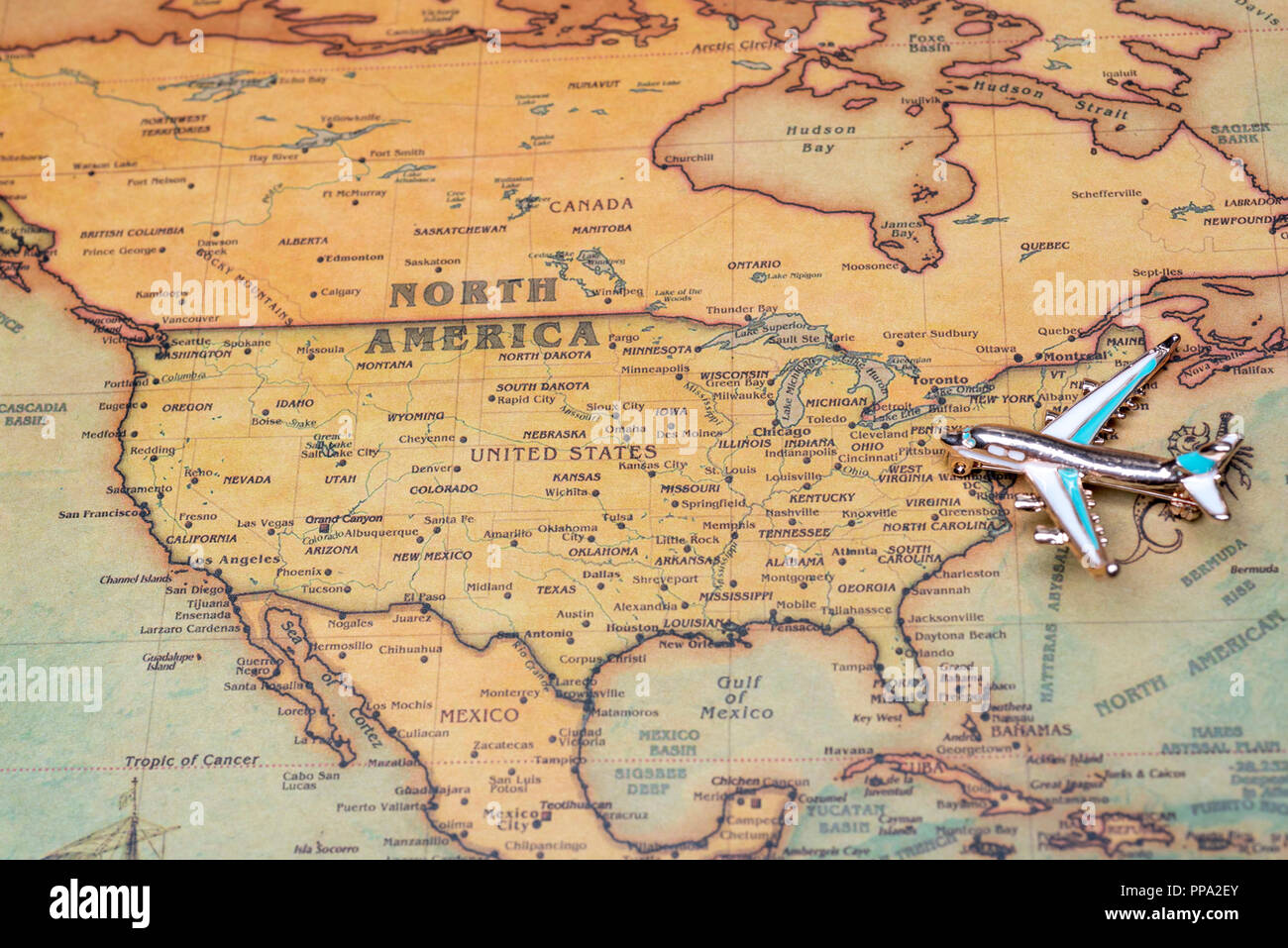 Airplane over a map of North America close-up. Toy airplane on the map background. - Stock Image