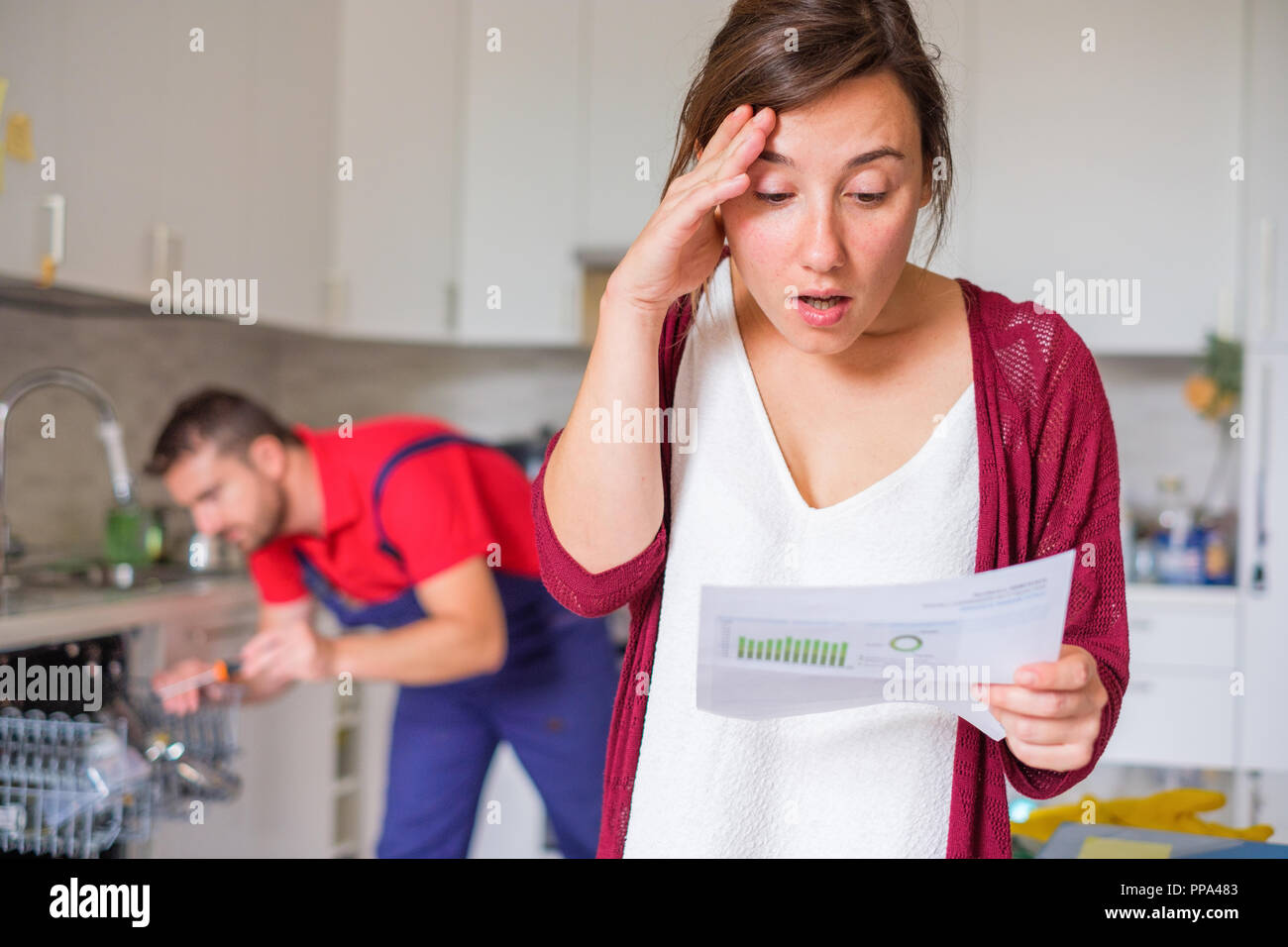 Housewife shocked after reading repair cost estimate of domestic appliance - Stock Image