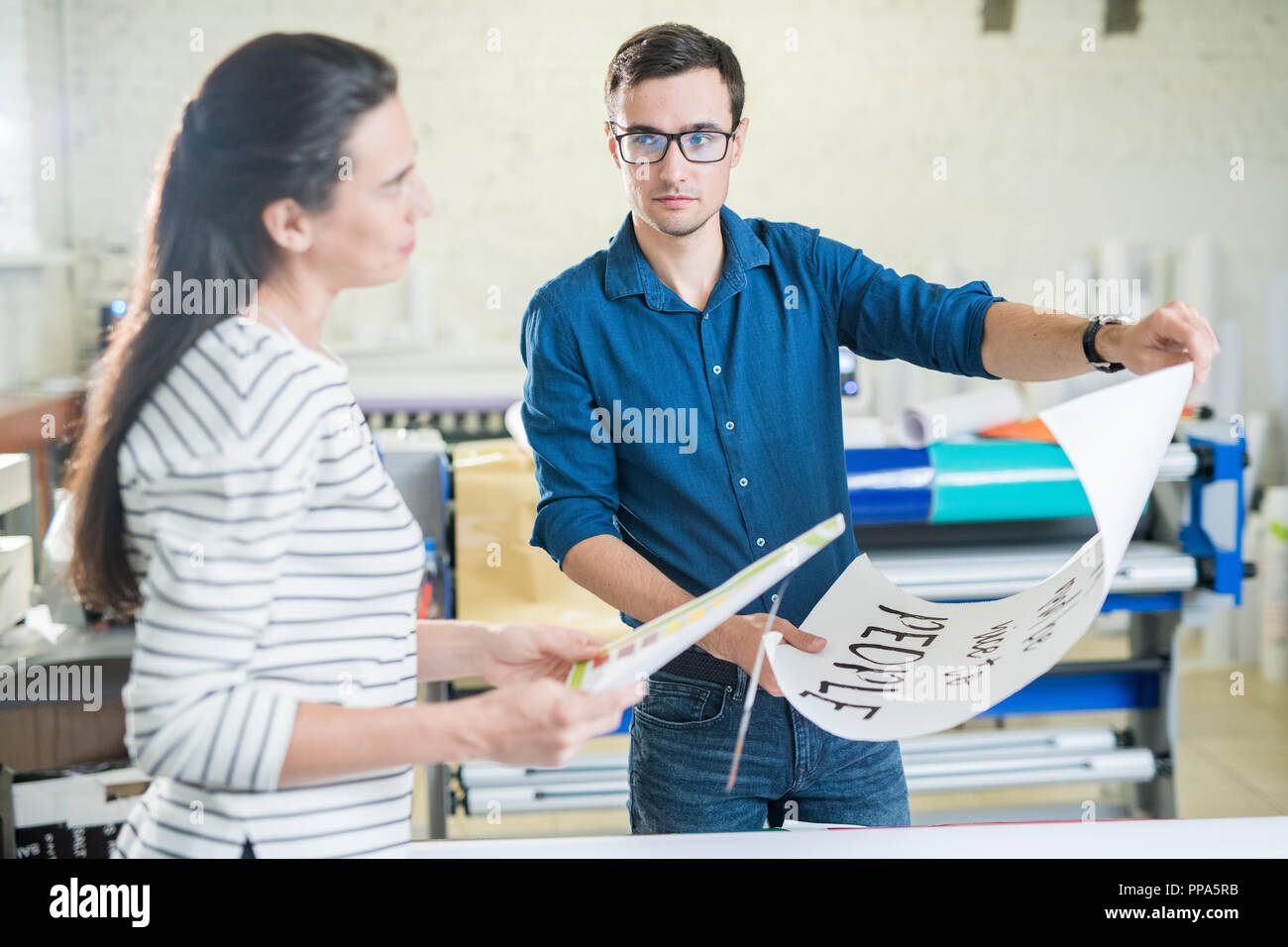 Coworkers of typography discussing placard - Stock Image