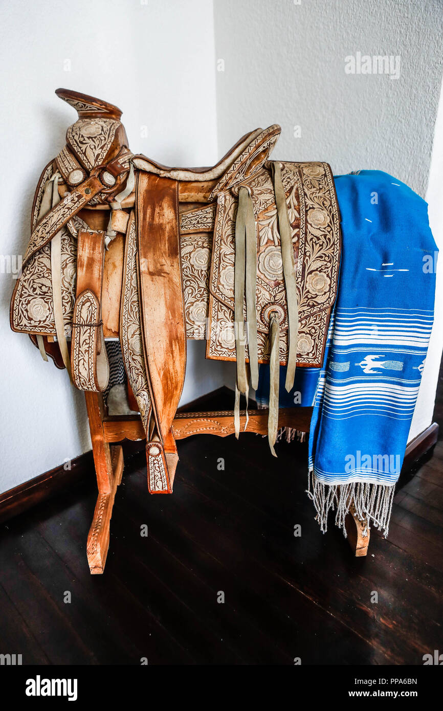 Zarape of blue color and Saddle. Decoration of the interiors of the Municipal Palace of Magdalena. leather chair, saddlery, charreria, mexican traditions, charro....Zarape de color azul y Silla de montar. Decoracion de los interiores de Palacio municipal de Magdalena. silla de piel, talabarteria, charreria , tradiciones mexicanas,  charro. (Photo: Luis Gutierrez / NortePhoto.com) - Stock Image