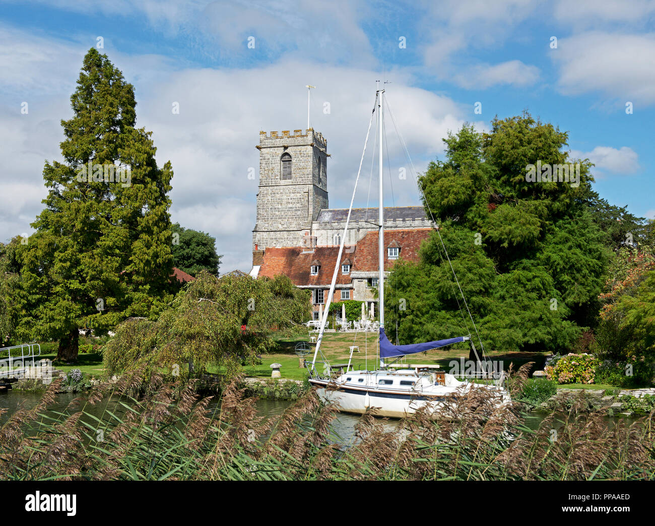 Sailing boat on River Frome, and Lady St Mary Church, Wareham, Dorset, England UK - Stock Image