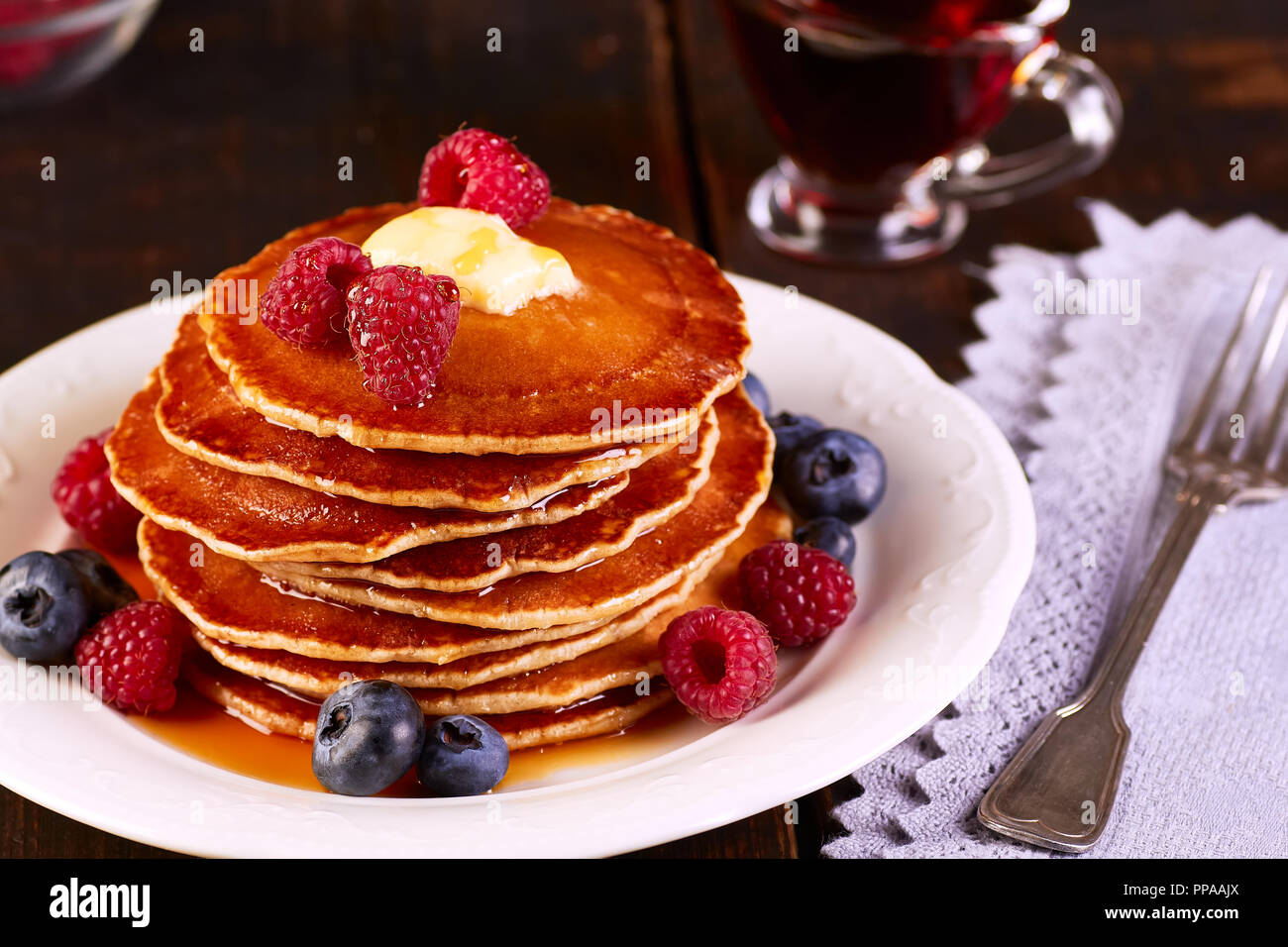 Pancakes with fresh berries and maple syrup on wooden table - Stock Image