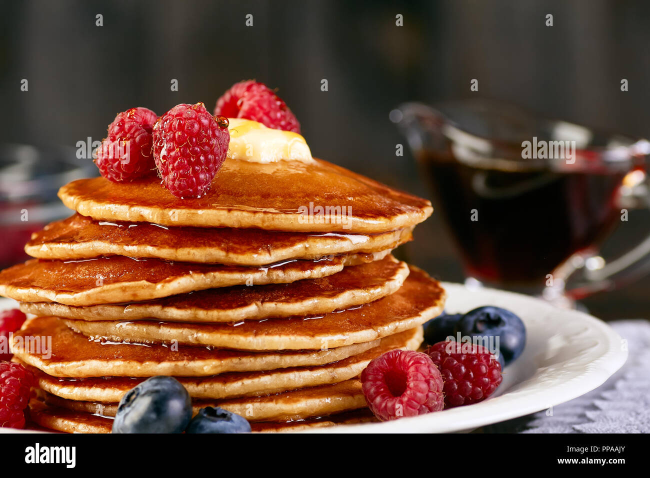 Stack of pancakes with berries and maple syrup - Stock Image