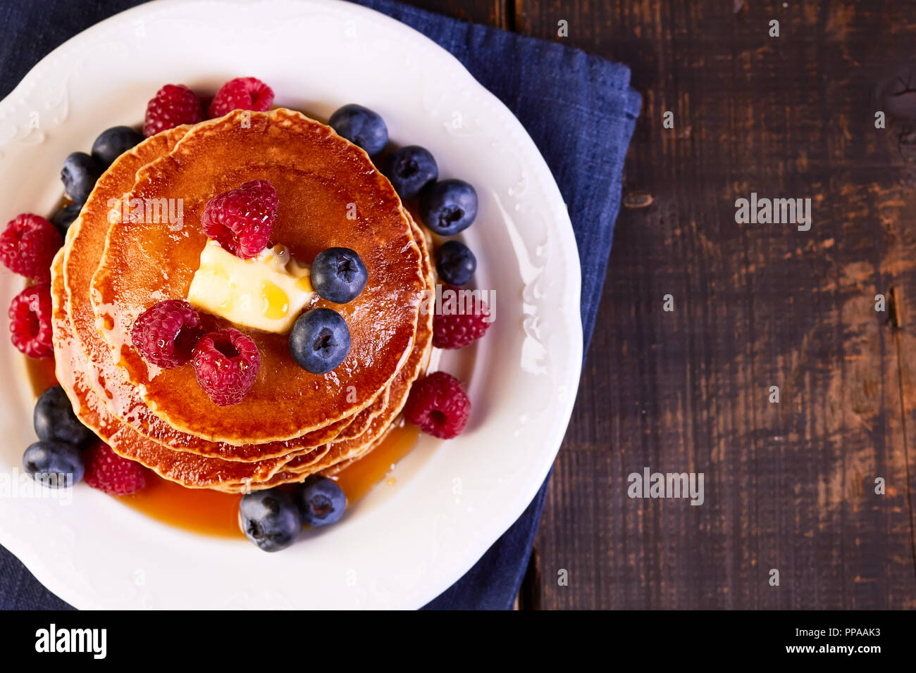 Pancakes with fresh berries maple syrup and butter on wooden table - Stock Image
