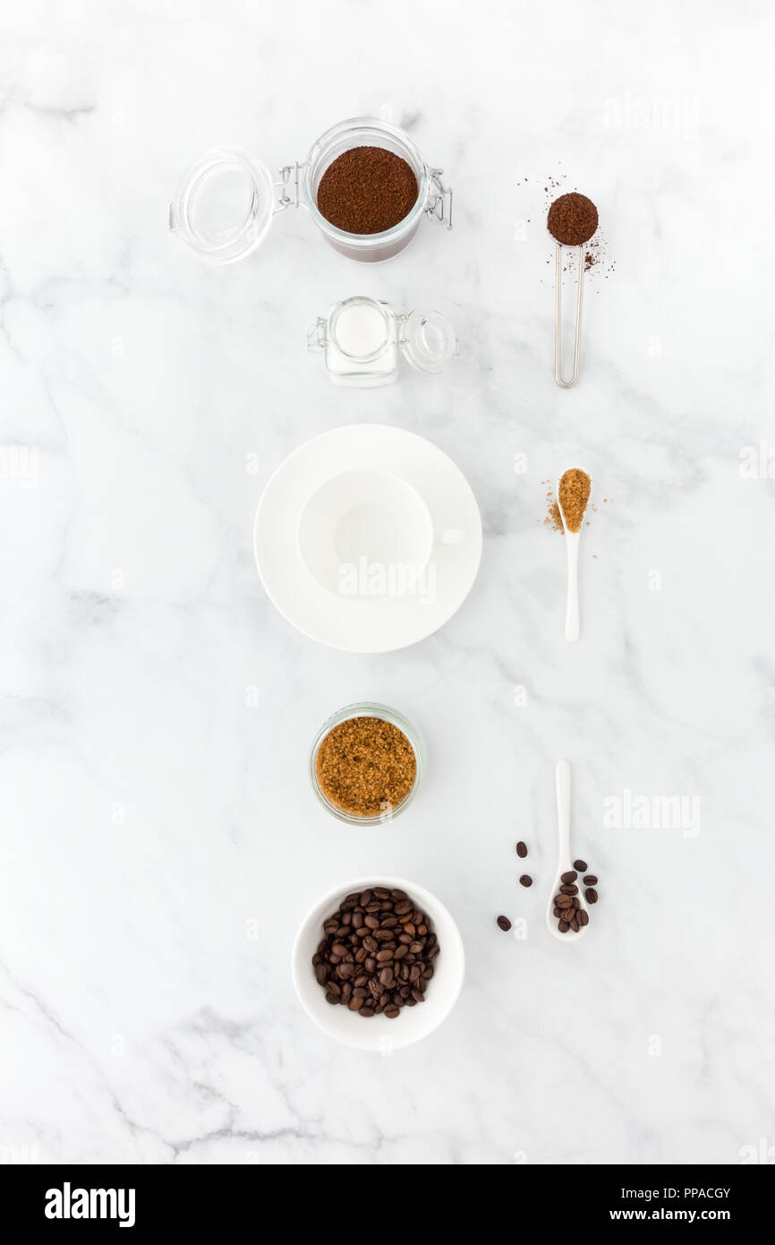 Coffee beans, ground coffee, brown and white sugar, coffee measuring spoon and an empty coffee cup on white marble background. - Stock Image