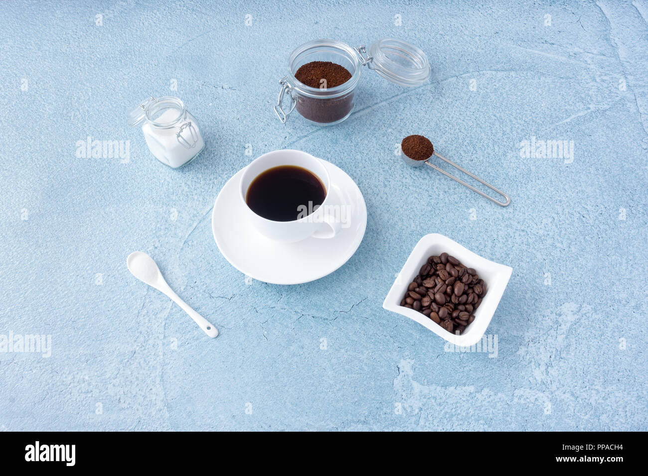 Coffee cup filled with black coffee, sugar, ground coffee and coffee beans on blue concrete background. - Stock Image
