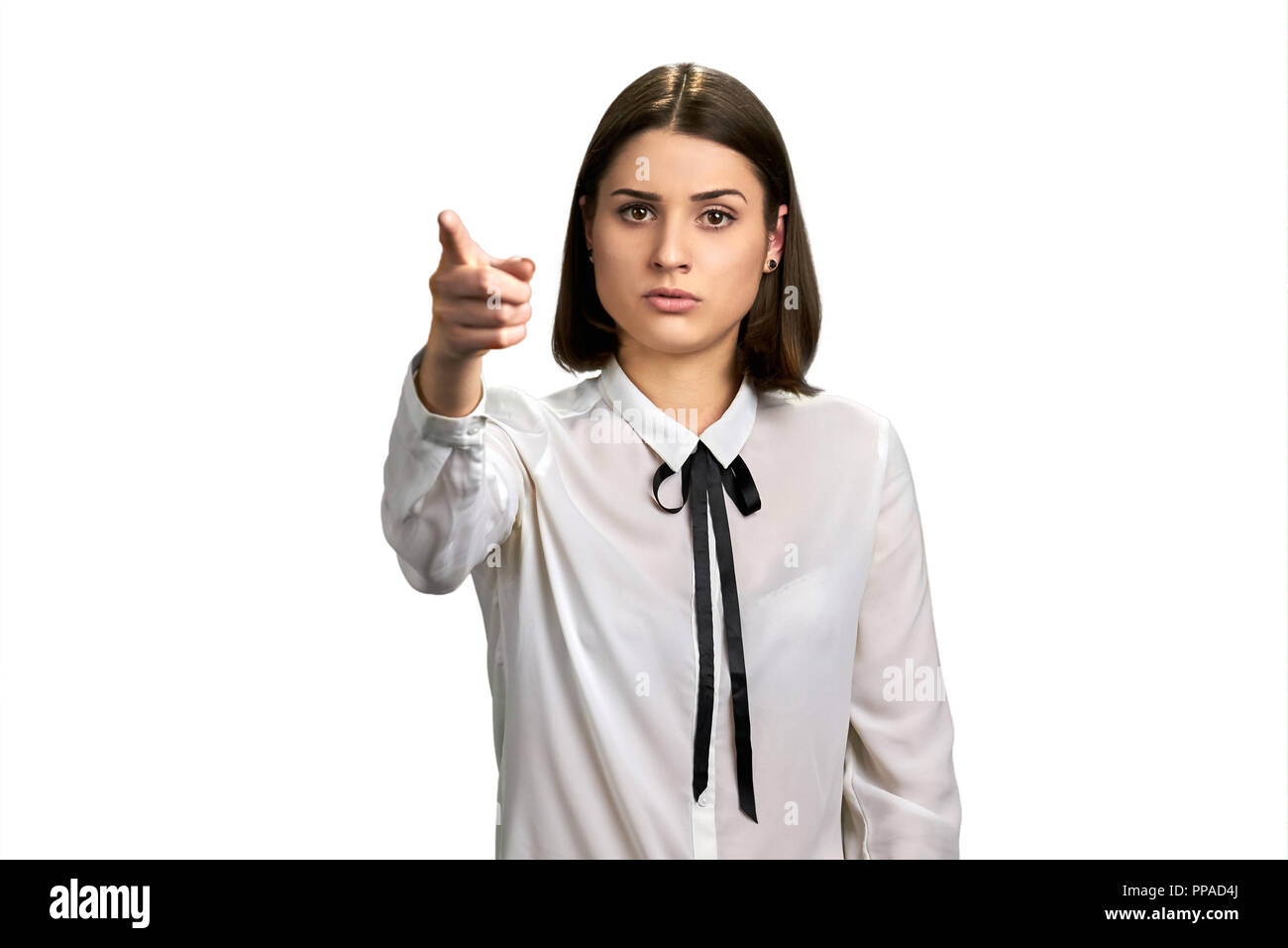 Confident young woman pointing forward. - Stock Image