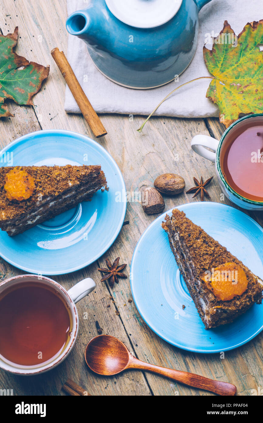 Carrot cake (homemade desserts) whith cinnamon sticks and decorated with spices and cup of tea on wooden background. - Stock Image