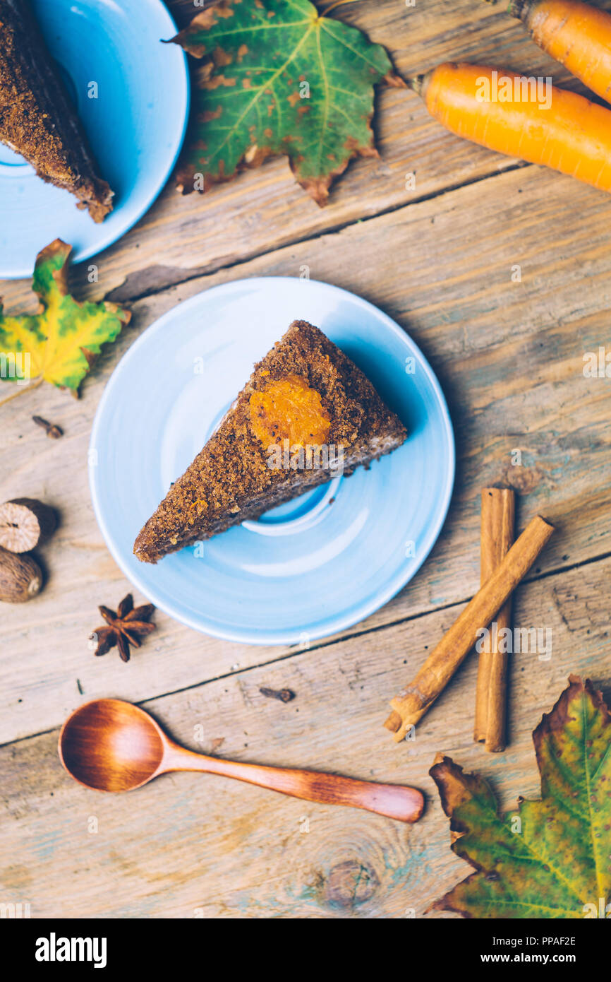 Carrot cake (homemade desserts) with cinnamon sticks and decorated with spices on wooden background - Stock Image