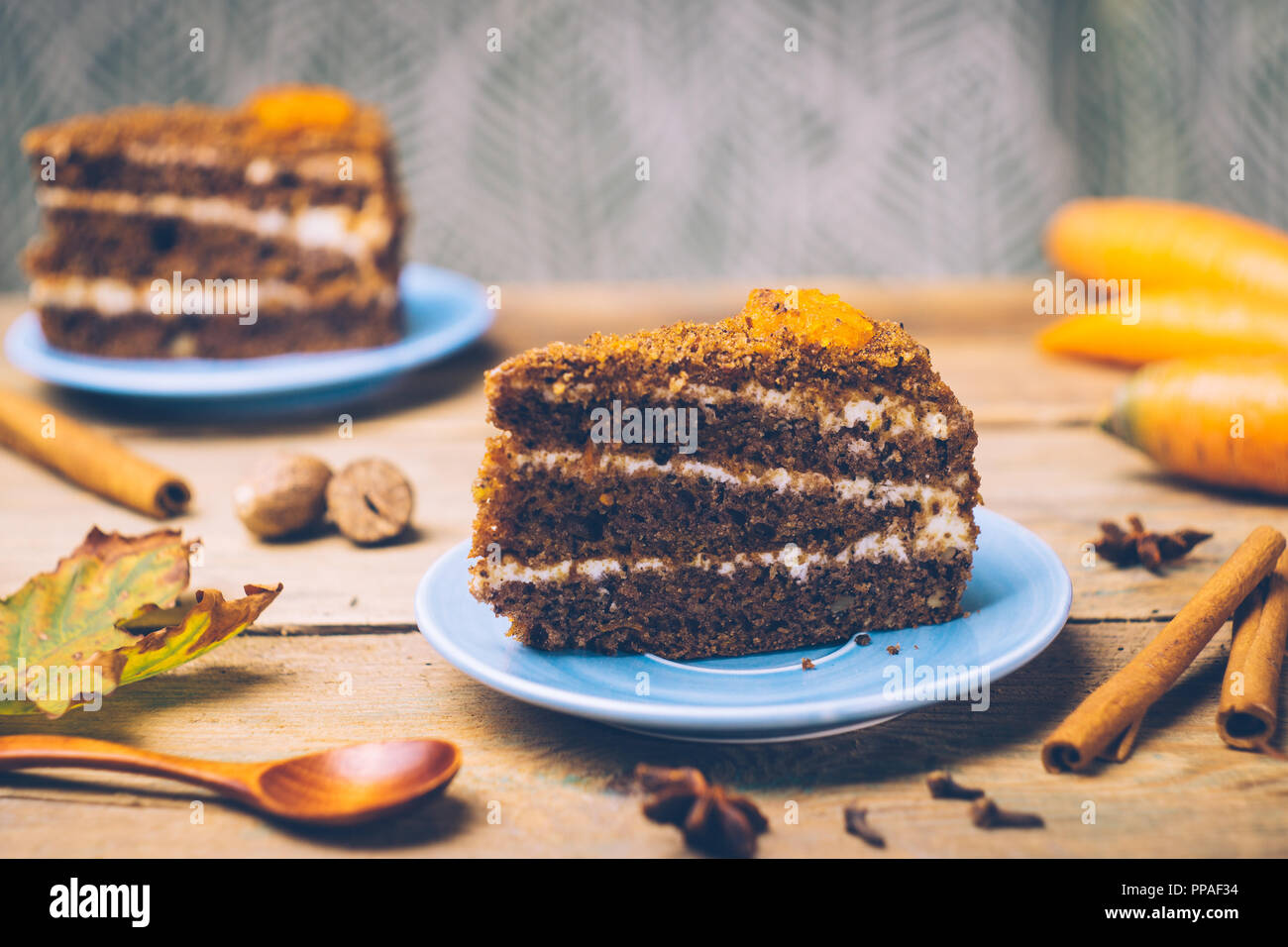 Carrot cake (homemade desserts) whith cinnamon sticks and decorated with spices on wooden background. - Stock Image