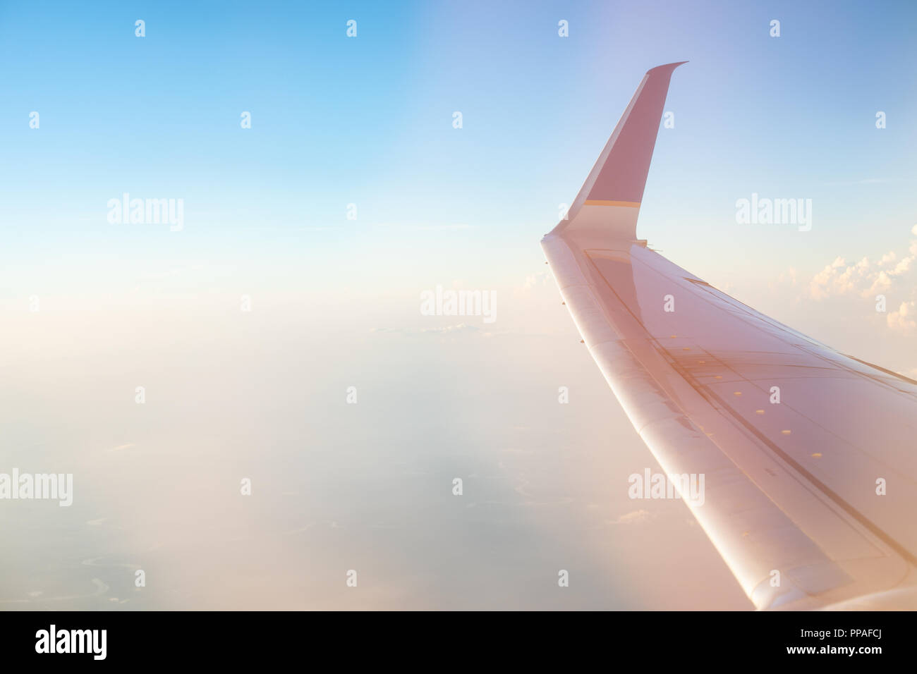 Stunning sunrise view on a high altitude from the passenger window of a conventional airplane. The morning sun colors the sky in pastel colors. - Stock Image