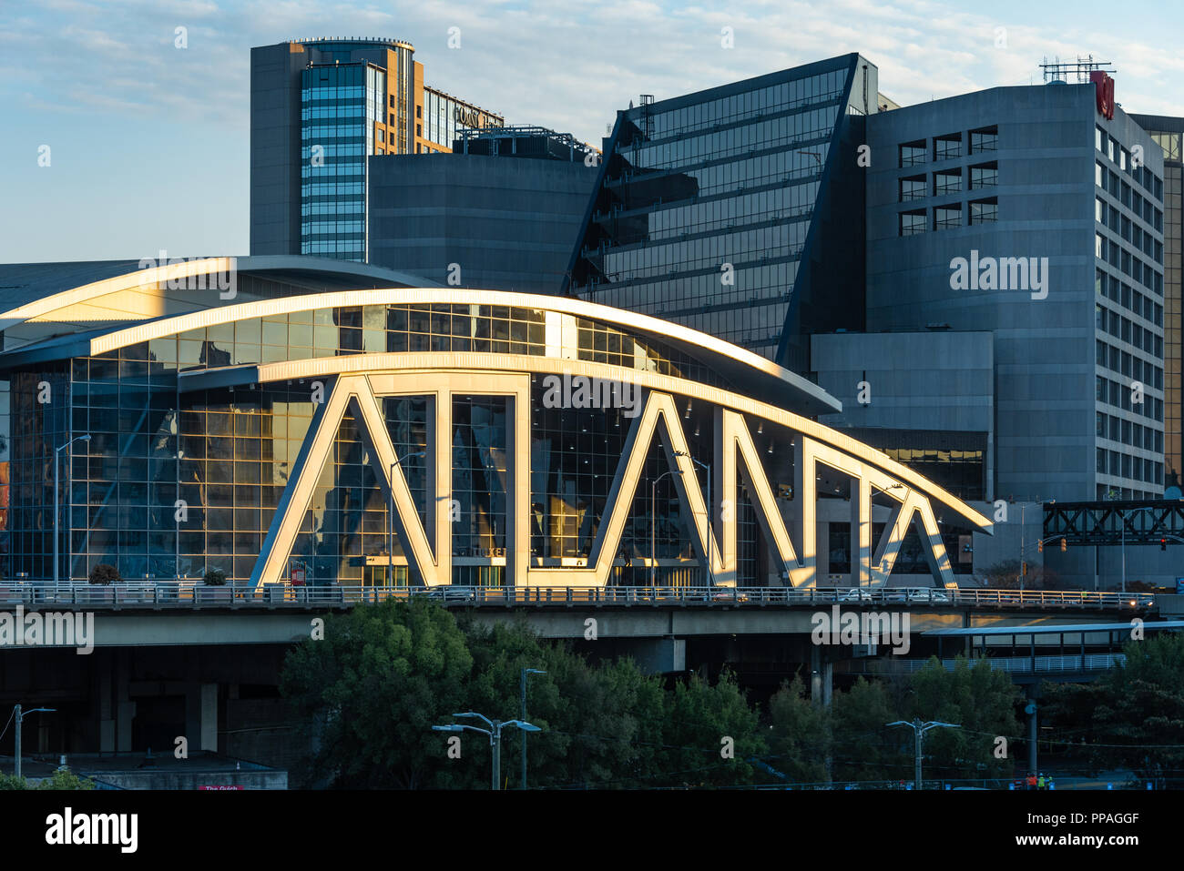 Atlanta Georgia's State Farm Arena, with its iconic typographic architecture, appears spotlit by the rising sun at sunrise. (USA) - Stock Image