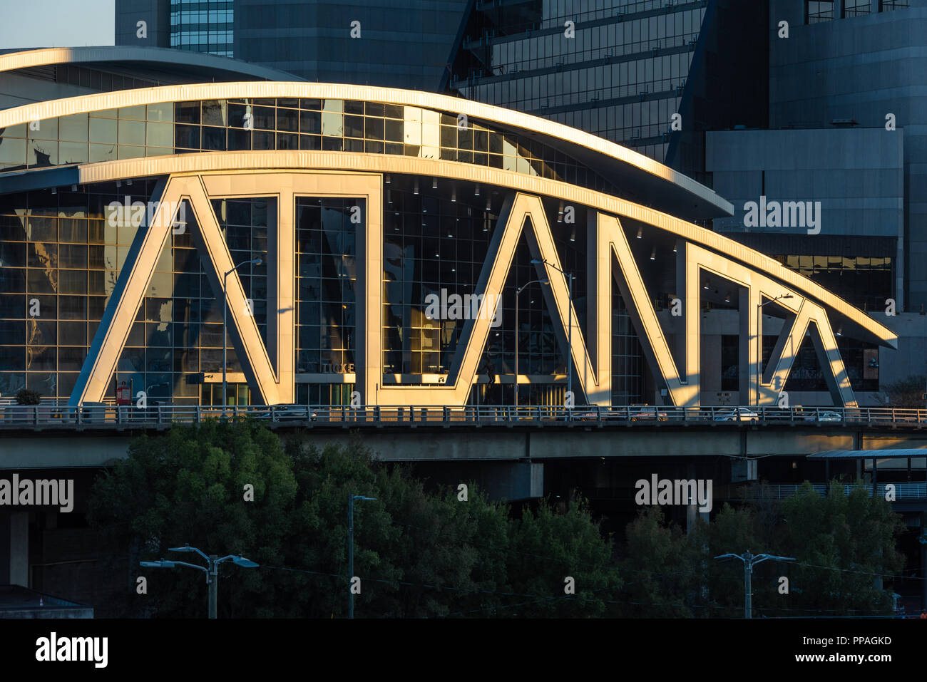 Iconic typographic architecture of the State Farm Arena appears spotlit by the rising sun at sunrise in downtown Atlanta, Georgia. (USA) - Stock Image