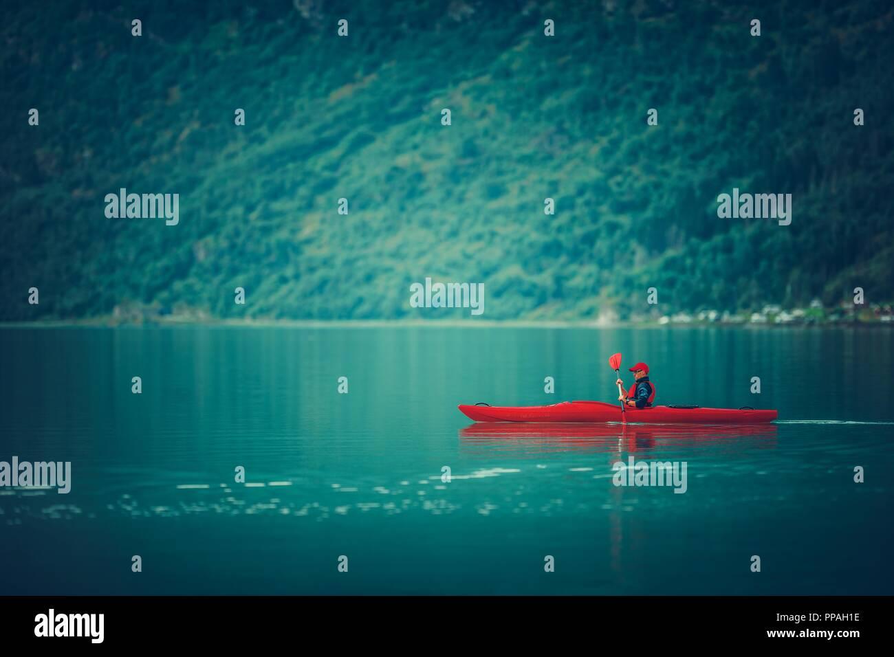 Glacial Lake Kayaking. Caucasian Sportsman Paddling in the Red Kayak. - Stock Image