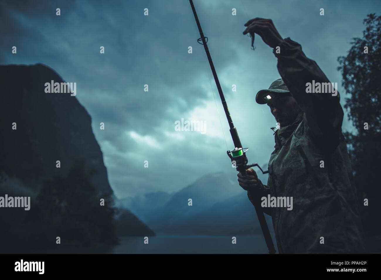 Late Rainy Evening Fly Fishing. Caucasian Fisherman Preparing His For Big Catch. - Stock Image