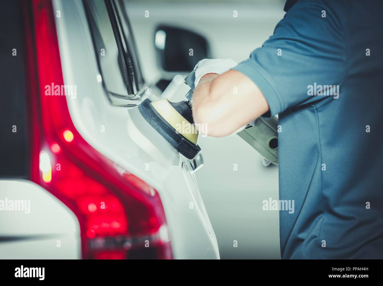 Professional Vehicle Buffing by Caucasian Car Detailing Service Worker. Removing Scratches From the Car Body Paint. Auto Polishing. - Stock Image