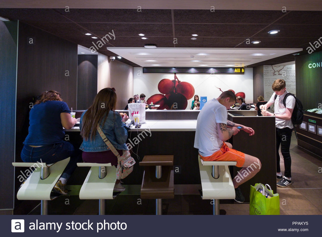 People sitting at counter inside McDonald's fast food restaurant, Grafton Street, Dublin, Leinster, Ireland - Stock Image
