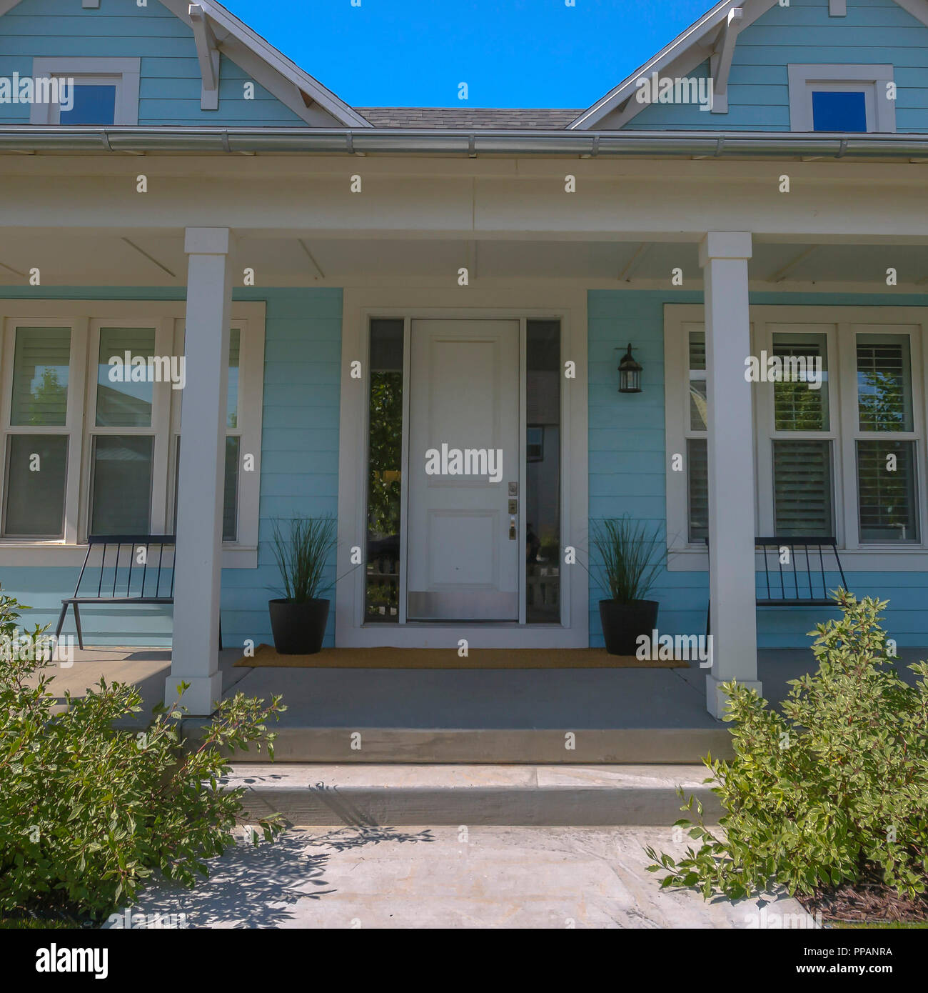 Facade of a home with white front door and columns - Stock Image