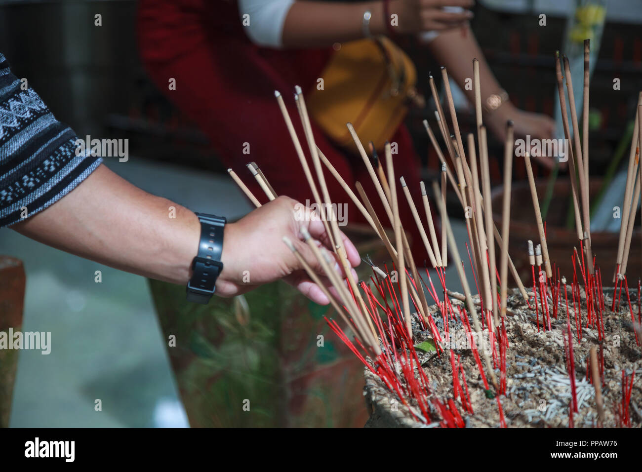 man hand sticks burning incense in incense pot in Buddhist Temple. Buddhism, Asian traditional religious ceremony, Rituals, Making a wish, Meditation, - Stock Image