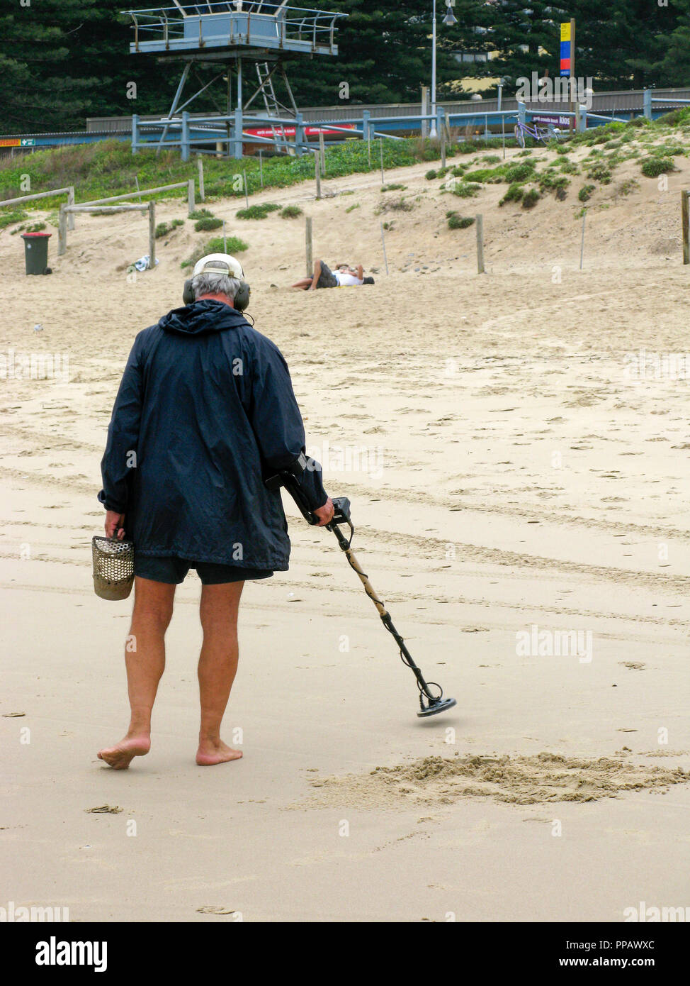 Man with METAL DETECTOR t a beach outside Sydney Australia,search for hidden metal objects - Stock Image