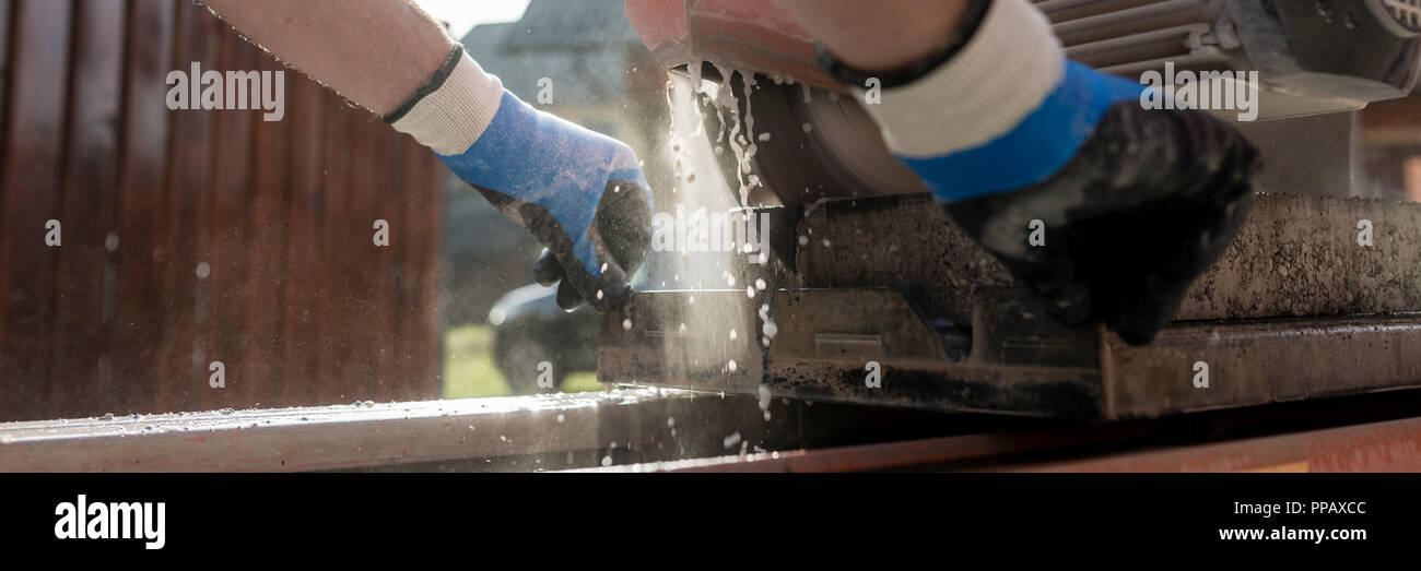 Low angle view of an angle grinder or circular saw cutting a paving slab or brick and the hands of a workman guiding the equipment. - Stock Image