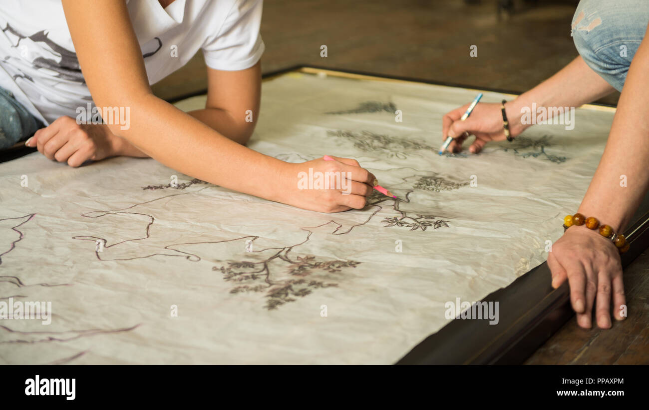 two girls painters draw a sketch through tracing paper, close-up - Stock Image