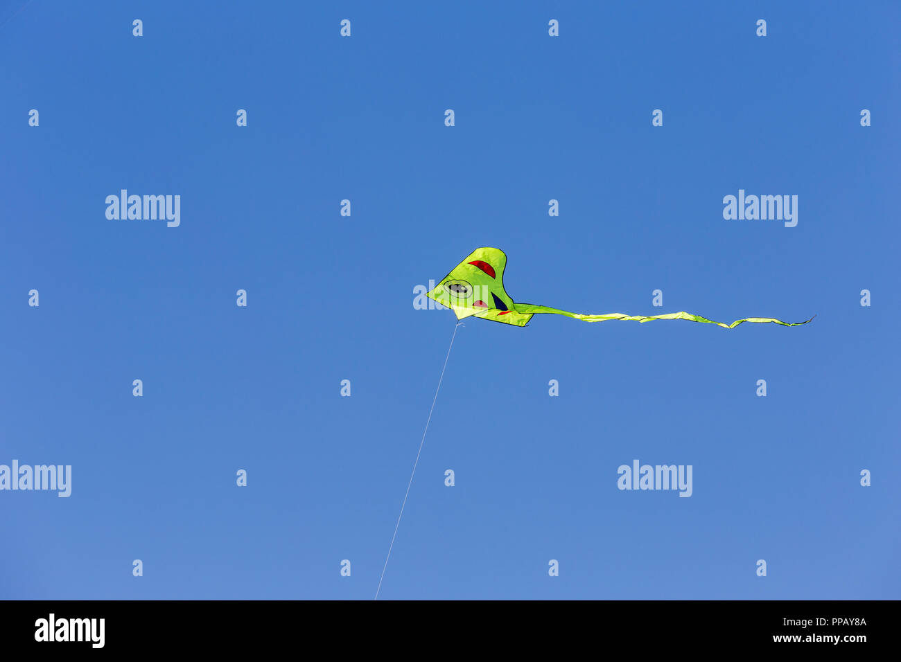 Yellow smiling face kite on the background of the summer open sky with copy space for text. Stock Photo
